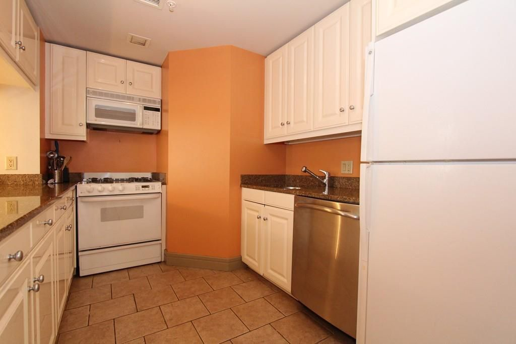 A small kitchen with a narrow U-shaped counter.