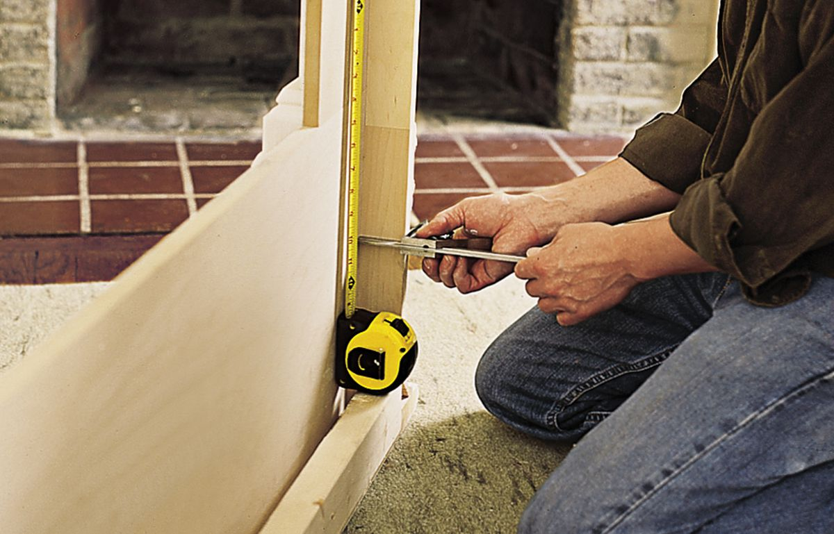 Man Positions Cleats Using Tape Measure