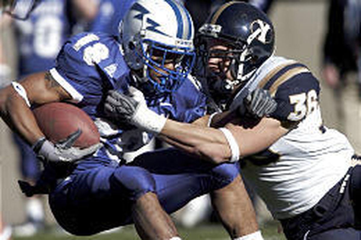 Air Force halfback Justin Handley is dragged down by BYU defender Markell Staffieri in the second half of the Cougars victory on Saturday.