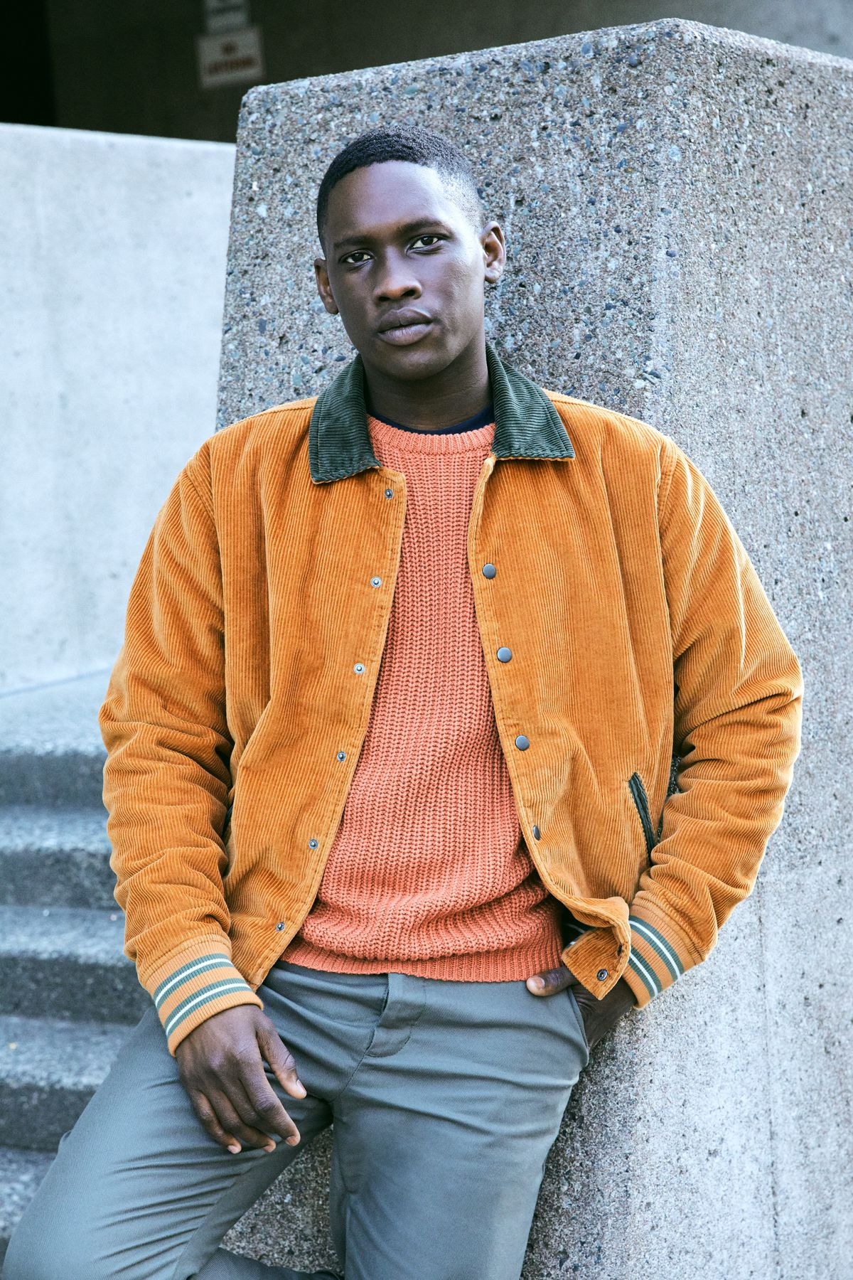 A male model poses outside a concrete building wearing an orange sweater, a corduroy jacket, and gray pants.