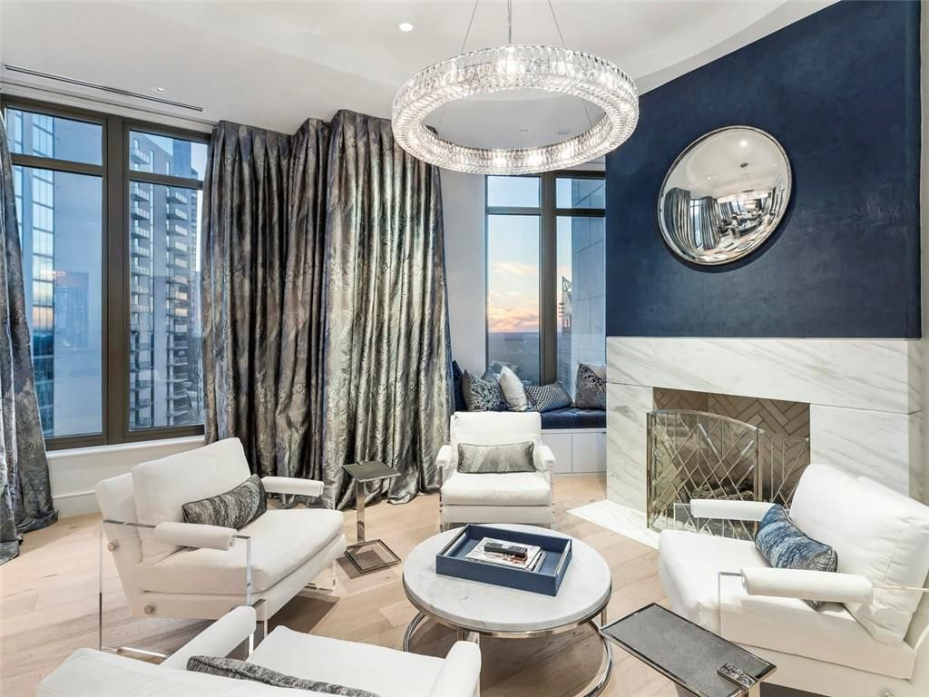 A white and blue living room with a fancy chandeliers.