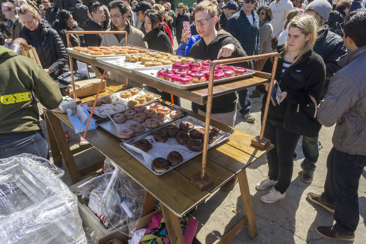 Visitors to food festival Smorgasburg look at a rack of colorful doughnuts