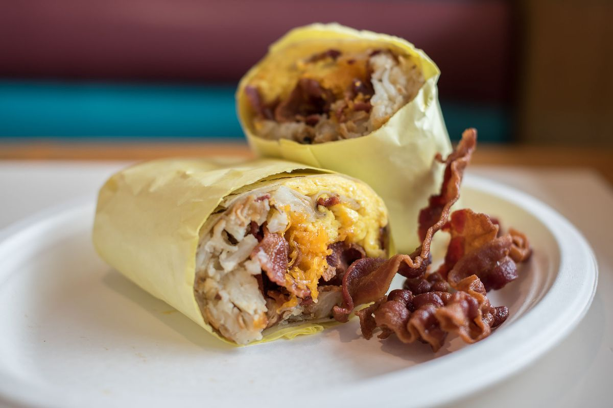 Breakfast Burrito with eggs and bacon in paper wrap on a white plate at Lucky Boy.