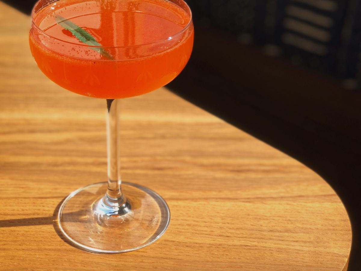 A red cocktail in a coupe glass.