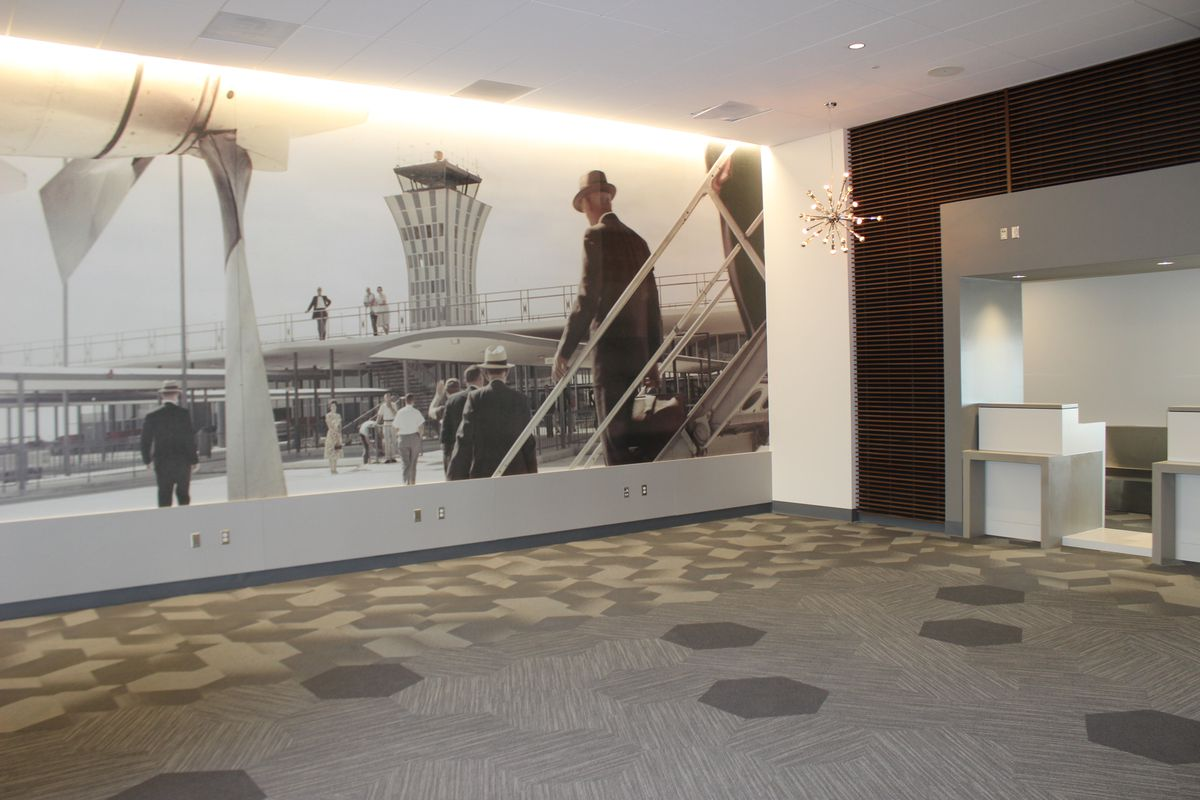 Black and white photo of airport in 50s, new mod carpeting, ticket counter