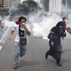 Protesters run as Police fire tear gas during an Anti Internal Security Act (ISA) demonstration in downtown Kuala Lumpur, Saturday.