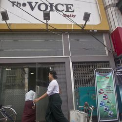 A school teacher walks by the office of The Voice Daily in Yangon, Myanmar, Monday, June 5, 2017. Police in Myanmar have arrested the newspaper's chief editor and a columnist for allegedly defaming the military by publishing an article mocking its role in the country's efforts to reach a peace agreement with fractious minority groups. A lawyer for The Voice Daily editor Kyaw Min Swe said Monday that the two were not released after being called in for questioning Friday over a lawsuit filed by the military under the country's Telecommunications Law.