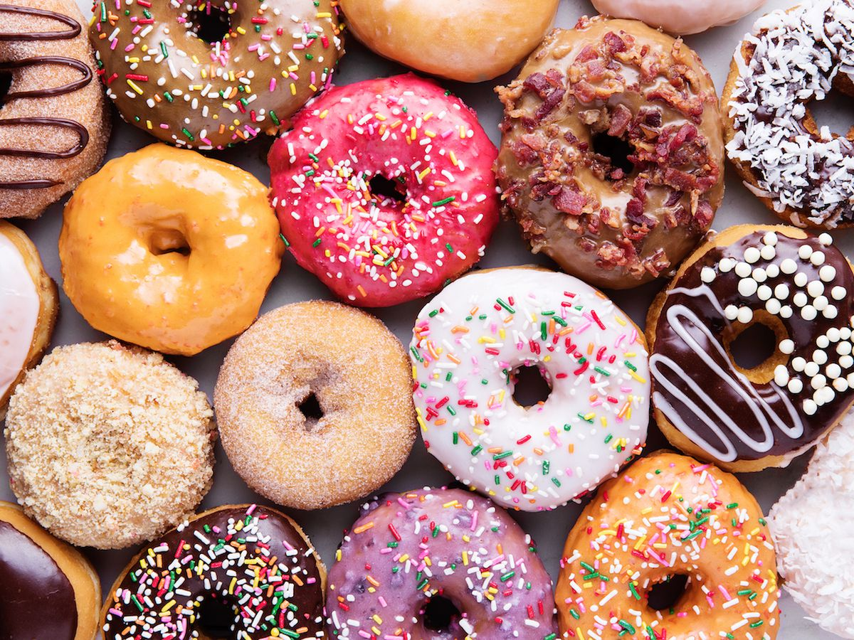 A colorful collection of doughnuts, glazed and sprinkled.