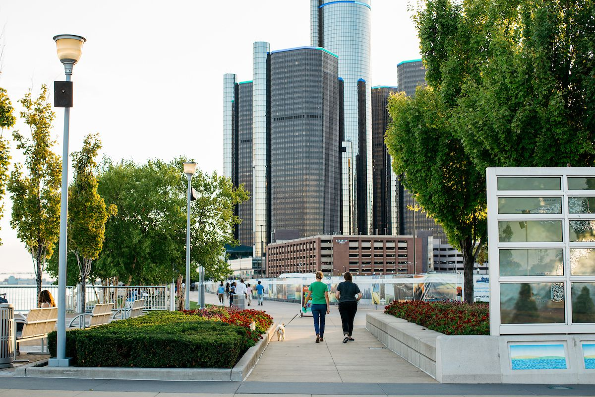 In the foreground is a path with people walking on it. The path has trees and grass on both sides of it. In the distance is a skyline with tall city buildings.