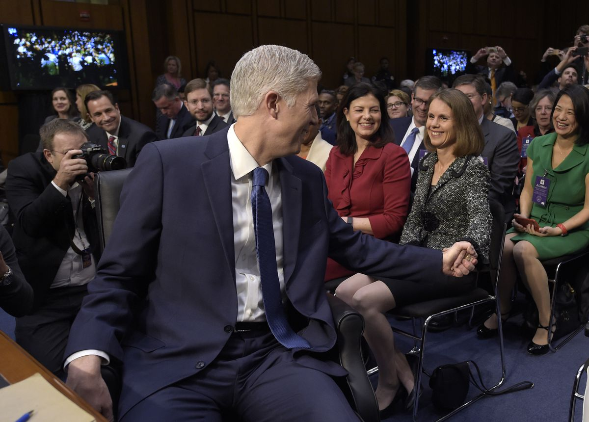 Supreme Court Justice nominee Neil Gorsuch, reaches back to hold the hand of his wife Marie Louise Gorsuch on Monday. Gorsuch was on Capitol Hill for his confirmation hearing before the Senate Judiciary Committee. | Susan Walsh/Associated Press