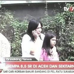 In this image made from Indonesian television TV One, a woman hugging a girl uses a mobile phone shortly after they ran out from a building when a strong earthquake hit in Aceh in Indonesia, Wednesday, April 11, 2012. A tsunami watch was issued for countries across the Indian Ocean after a large earthquake hit waters off Indonesia on Wednesday, triggering widespread panic as residents along coastlines fled to high ground in cars and on the backs of motorcycles.