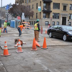 Plates being put into place to secure the work area on Waveland in front of Murphy's