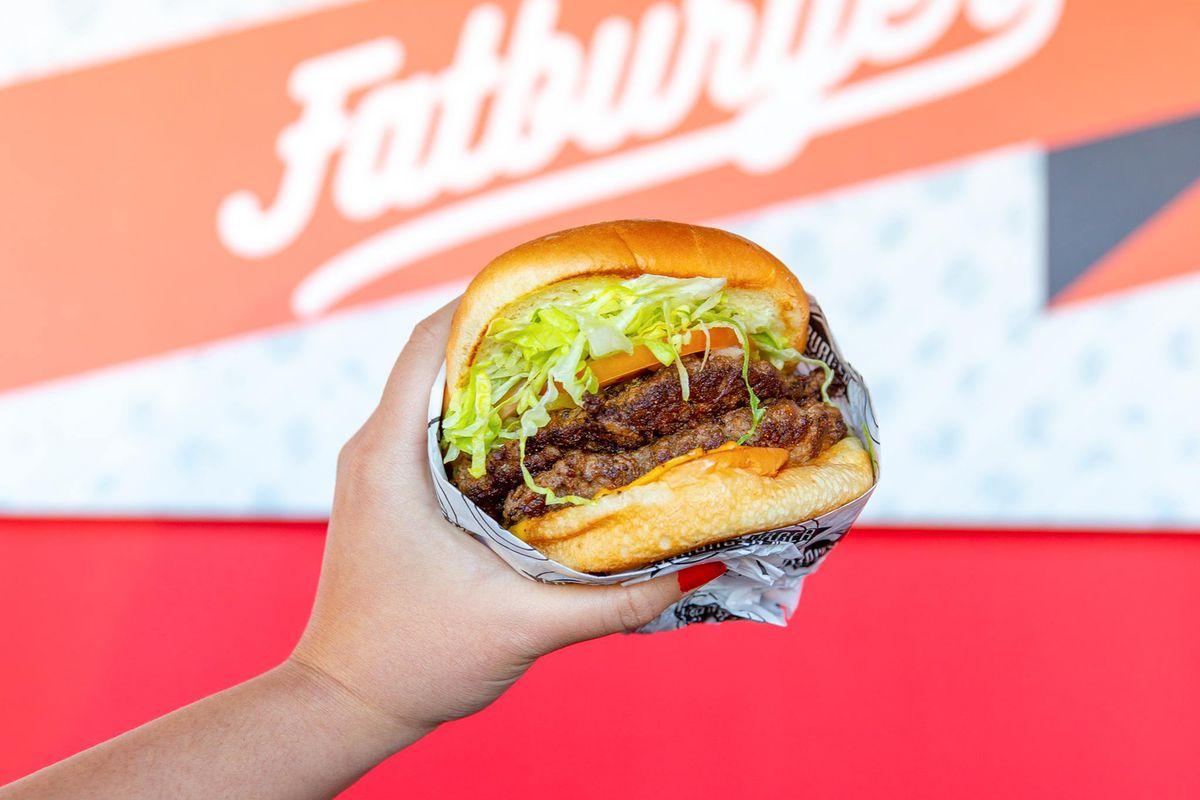 A hand holding up a semi-wrapped burger with shredded lettuce, a tomato slice, two patties, and cheese in front of a Fatburger sign