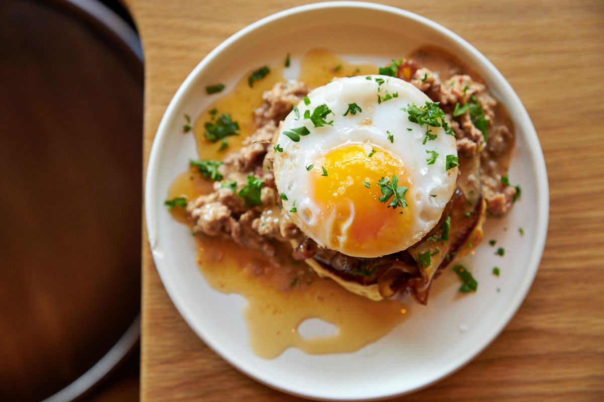 A stack of pancakes with a duck egg and duck sausage gravy at Canard