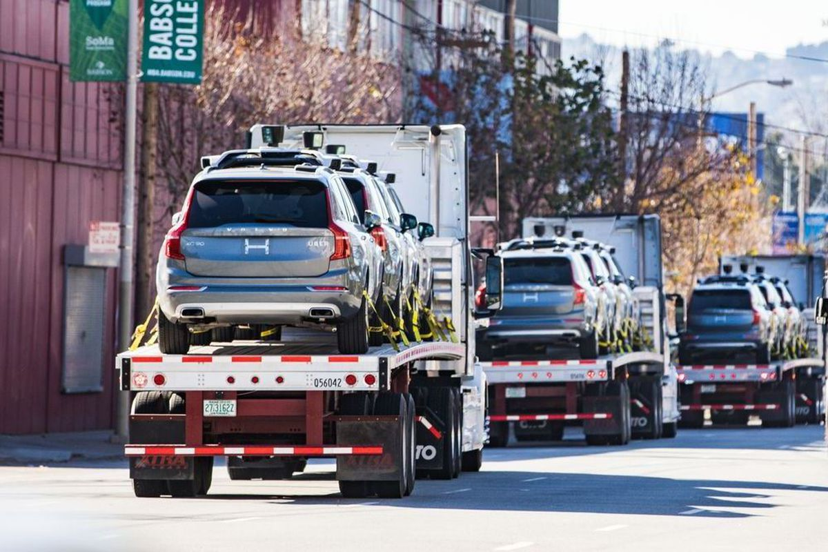 Self-driving cars loaded onto the back of trucks, departing.