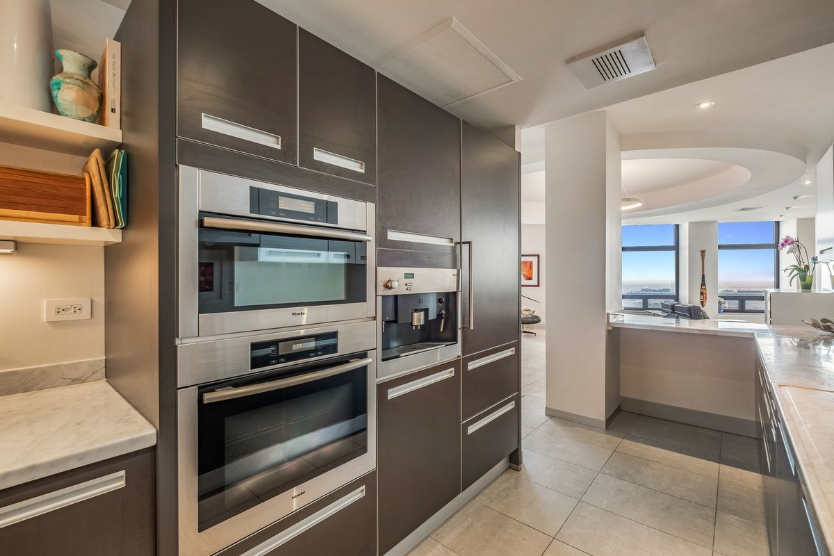 A small galley kitchen with white countertops, smooth brown cabinets, and stainless steel appliances.