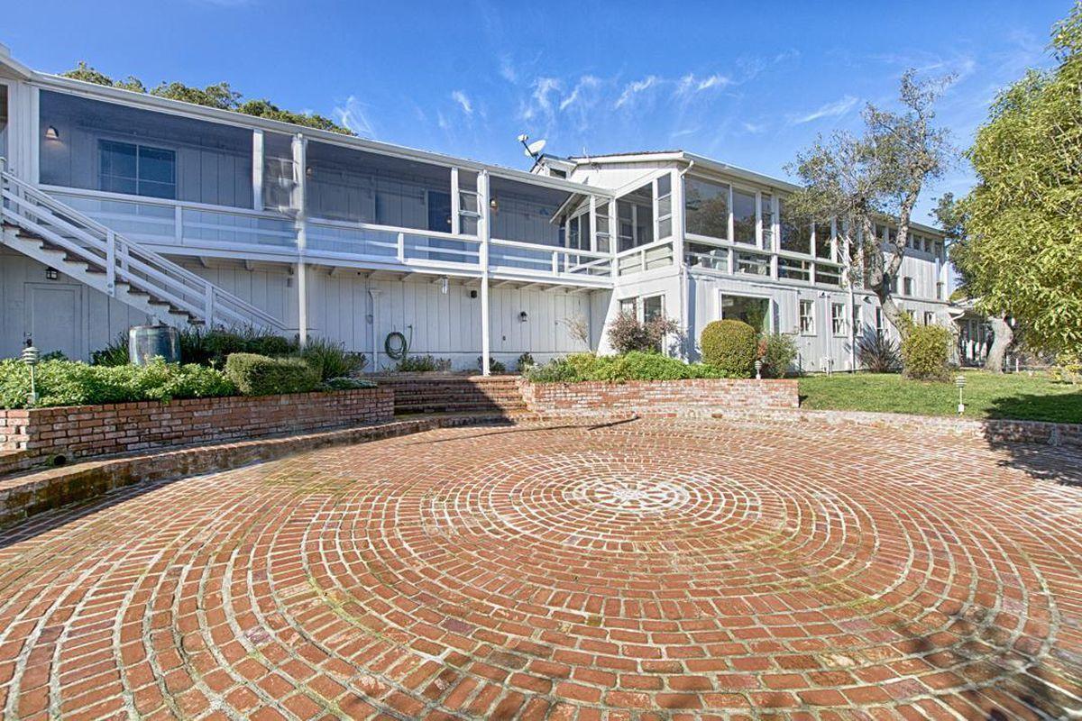 Facade of white house in Santa Cruz with gorgeous circular brickwork driveway