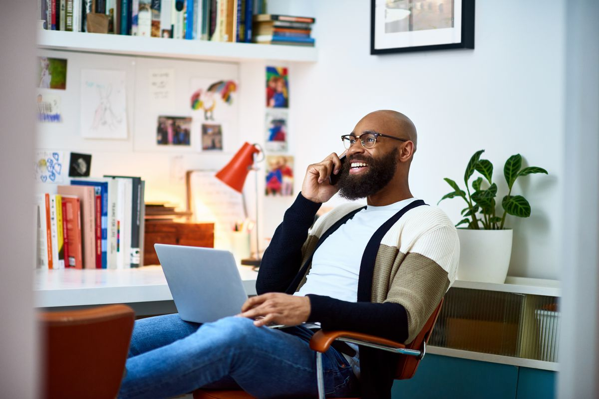 A smiling man is on the phone, sitting in a home office with his laptop on his lap.