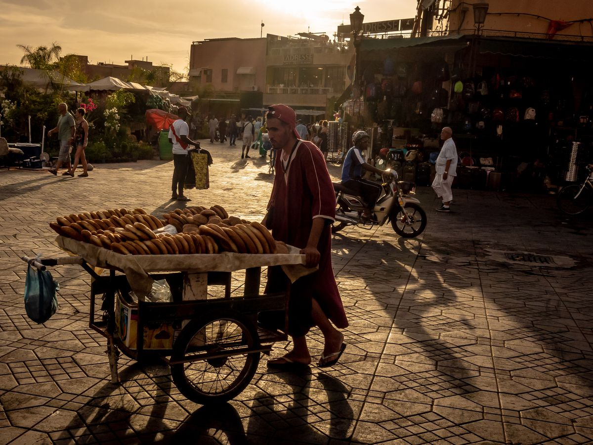 A street vendor pushes a cart of flatbreads on decorative streets in the early morning sun, with tourists and locals walking in the background, market stalls loaded with merchandize, and riders on motorbikes pass by.