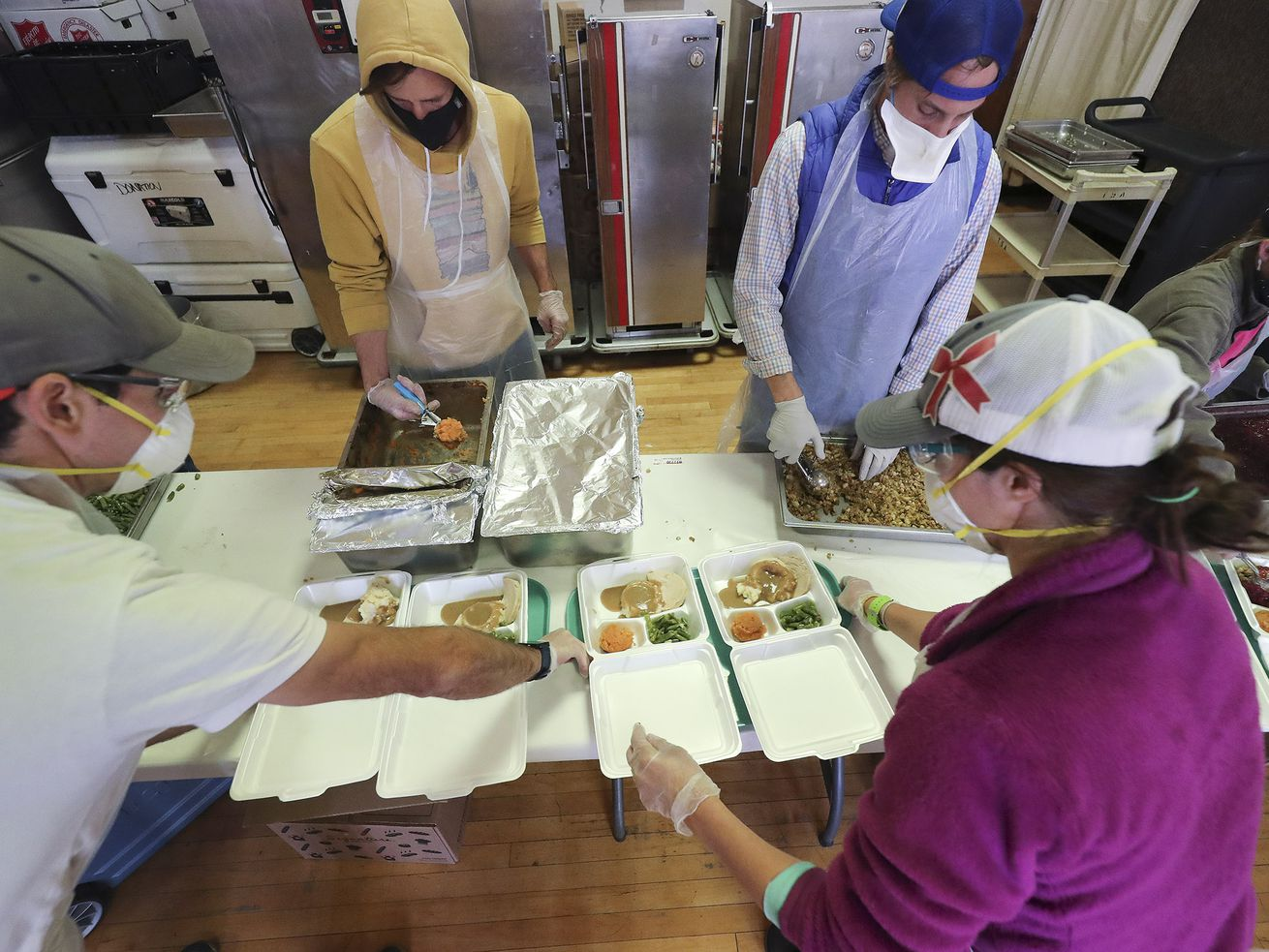 Volunteers Derek Storrs, Marcus Cline, Jamen Nelson and Katie Storrs assemble traditional Thanksgiving dinners at the Salvation Army in Salt Lake City on Thursday, Nov. 26, 2020, for 800 needy people throughout the Salt Lake Valley.