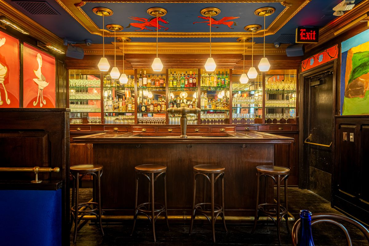A small wooden bar set for service inside of a dark blue dining room at an old restaurant.