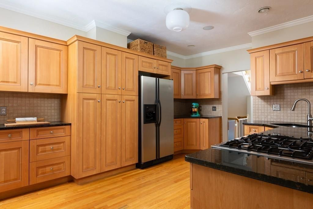 A kitchen with a large cabinet next to the fridge and an L-shaped counter.