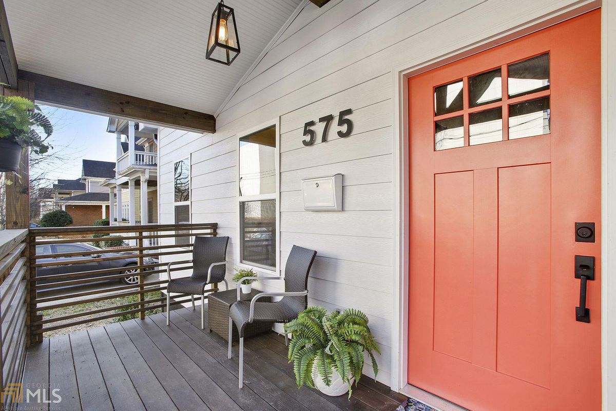 Front porch with two chairs and a plant next to the coral-colored front door.