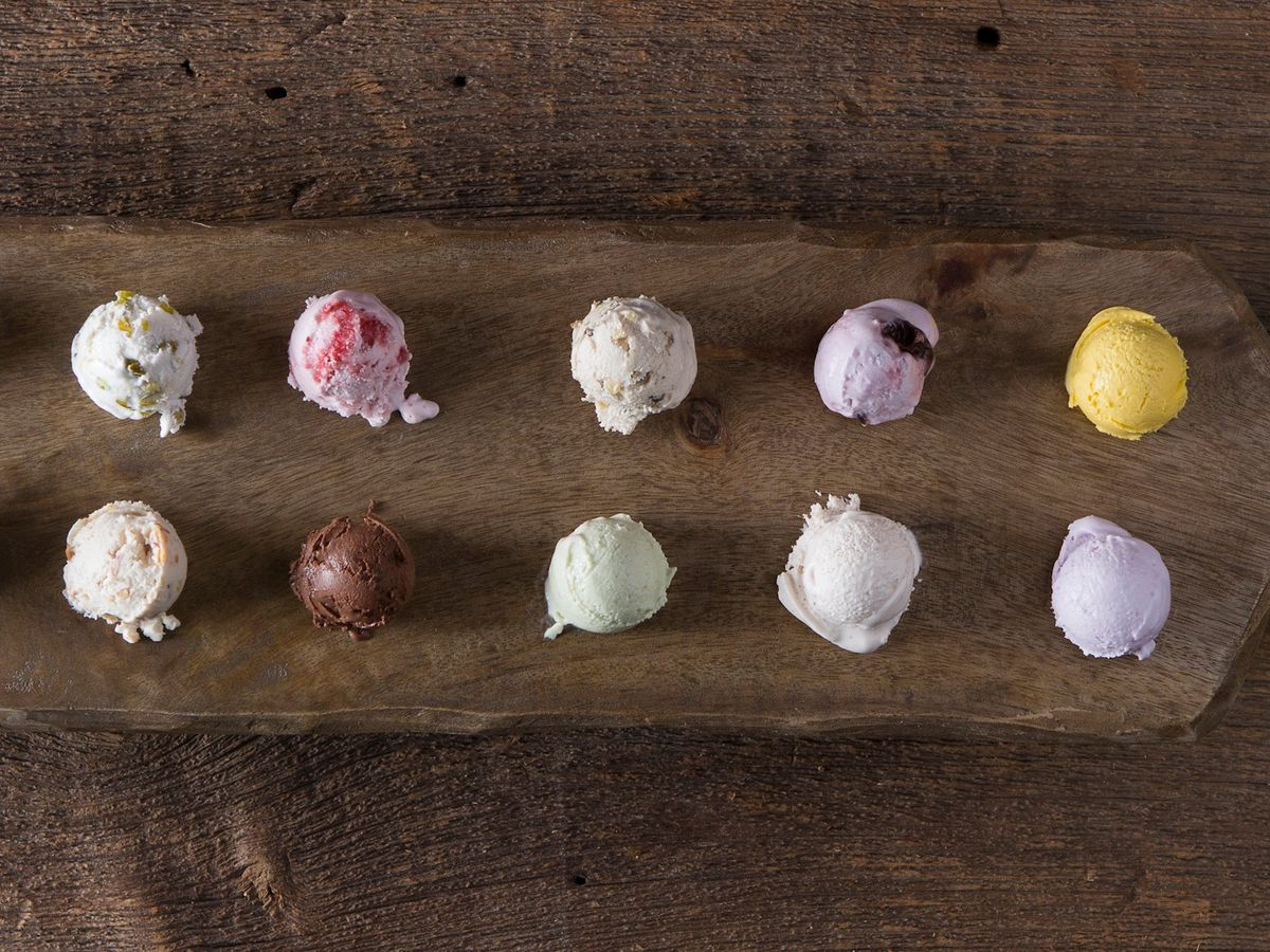 Overhead shot of a wooden paddle on a wooden table. 12 colorful scoops of ice cream line the paddle in two rows.