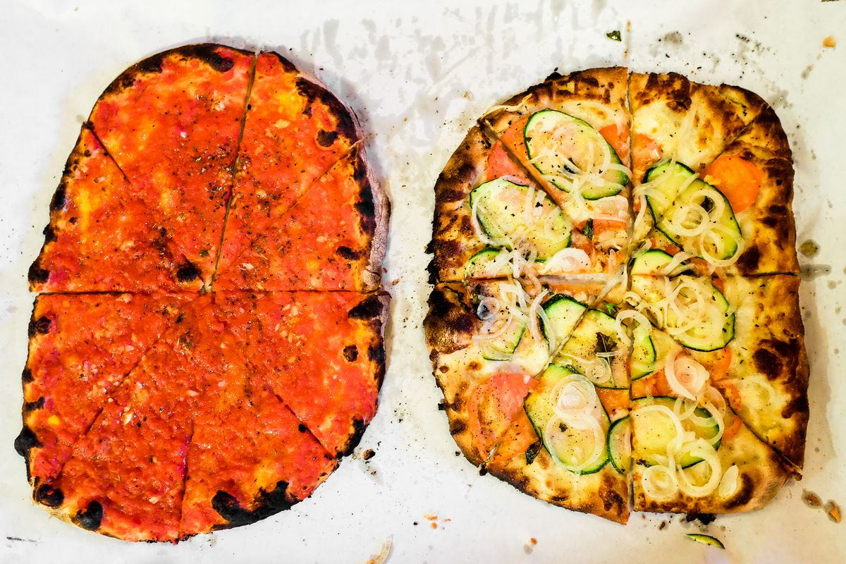 Overhead view of two thin-crust, New Haven-style pizzas on white paper. They feature charred crust and a slight asymmetry. One has a simple tomato topping (no cheese), one is a white pizza with thinly sliced zucchini, onions, and basil.