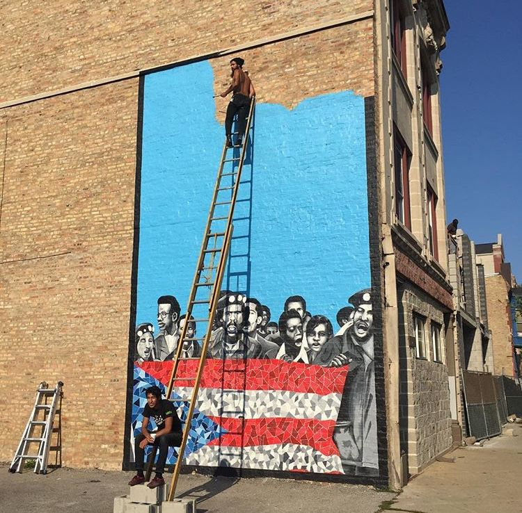 """Luis Raúl Muñoz, at the top of a ladder, painting """"Our Story of Resilience"""" in Humboldt Park."""