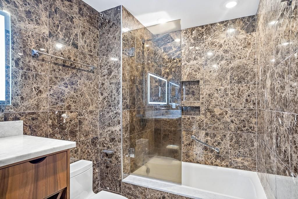 A bathroom with a shower with a partial glass door.