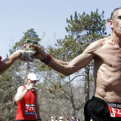 Paul Kmiecik, right, of Middleton, Wisc., grabs a cup from a watering station during the Boston Marathon in Wellesley, Mass., Monday, April 16, 2012.  It was the second-slowest Boston race since 1985, as temperatures rising into the 80s slowed the leaders and may have convinced as many as 4,300 entrants to sit this one out.  (AP Photo/Michael Dwyer)