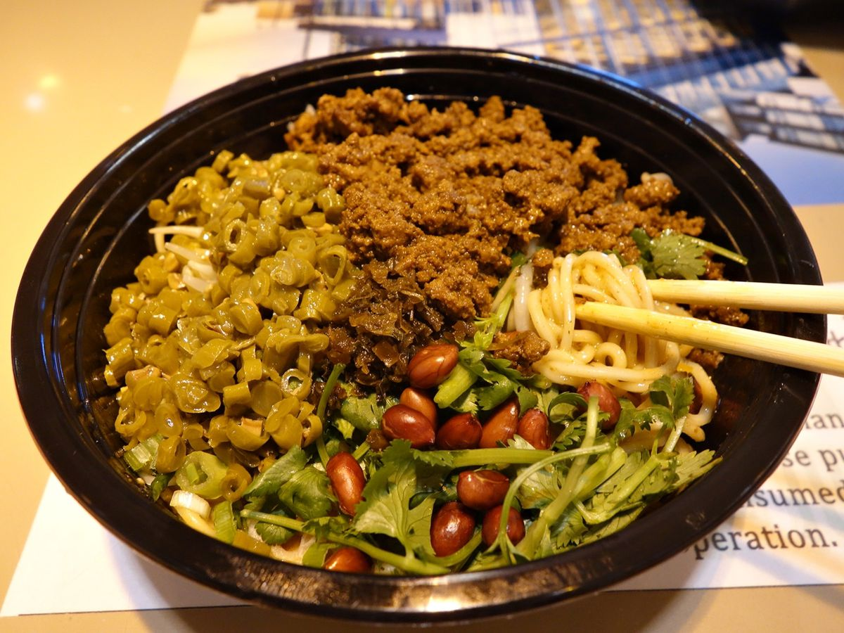 A closeup view of a noodle dish with ground meat, greens, and nuts.