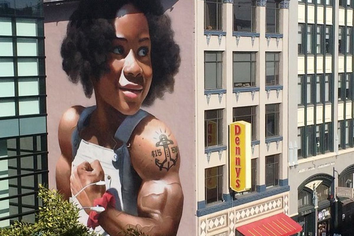 """A four-story mural of a young African American girl with a determined and cheerful expression and an anchor tattoo on her shoulder reading """"415-510."""""""