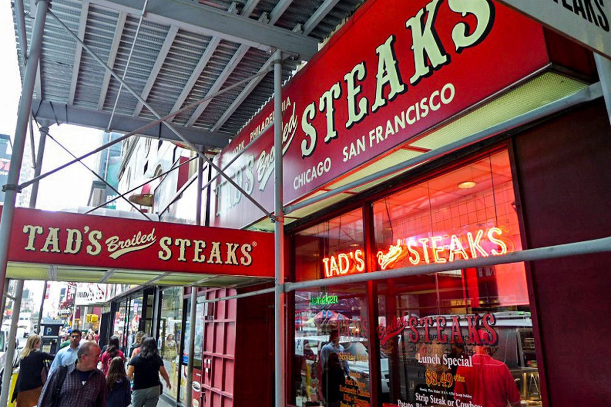 The exterior of Tad's Steak, which has a red awning and an old-timey font.
