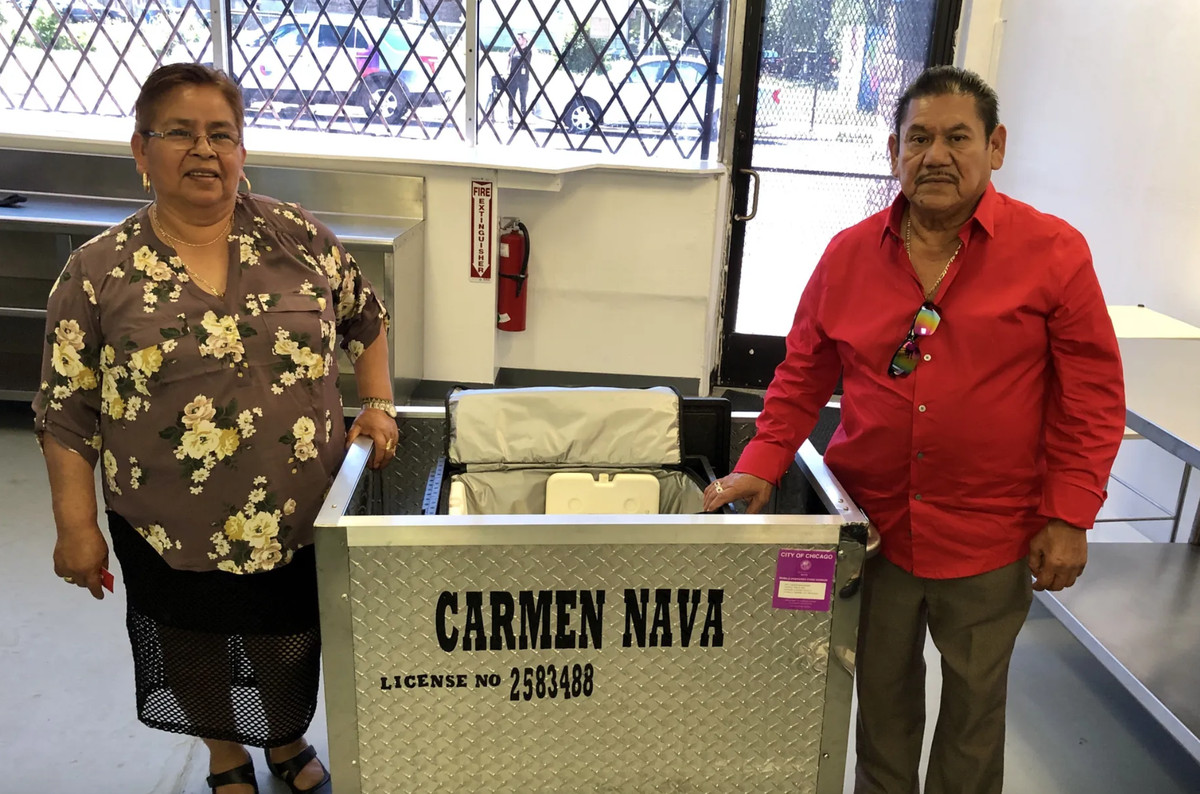 A man and woman stand in front of a licensed street cart