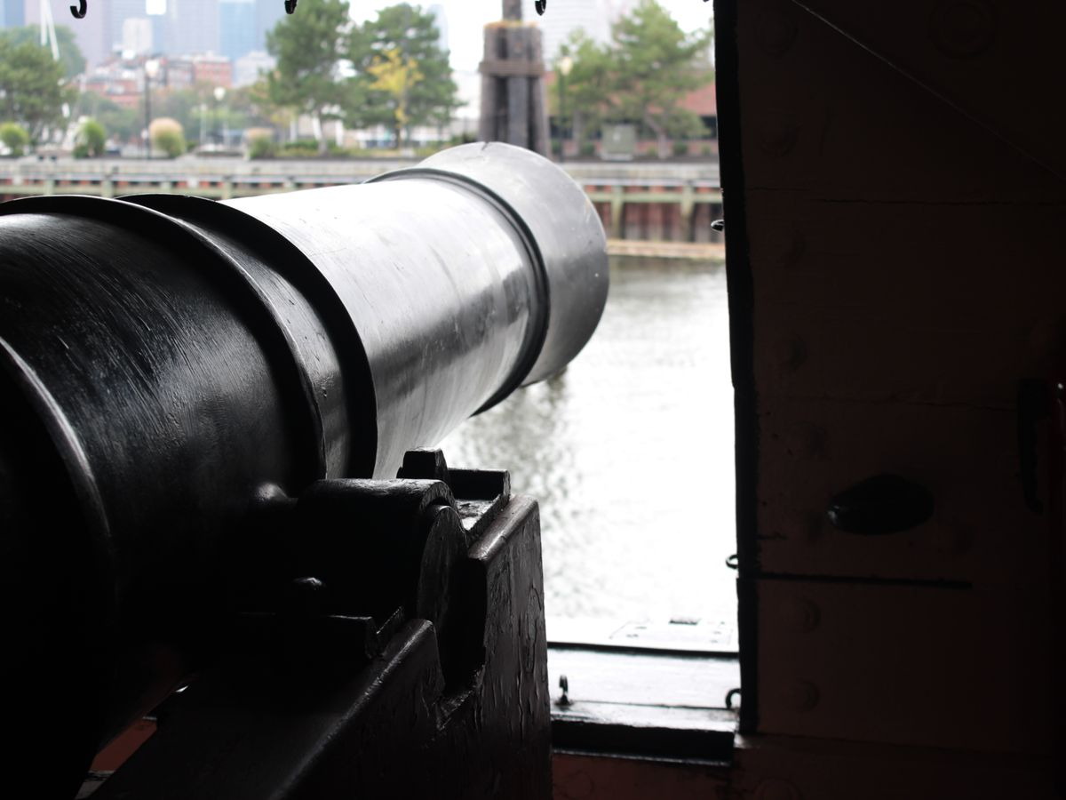A cannon facing away from a ship hole.