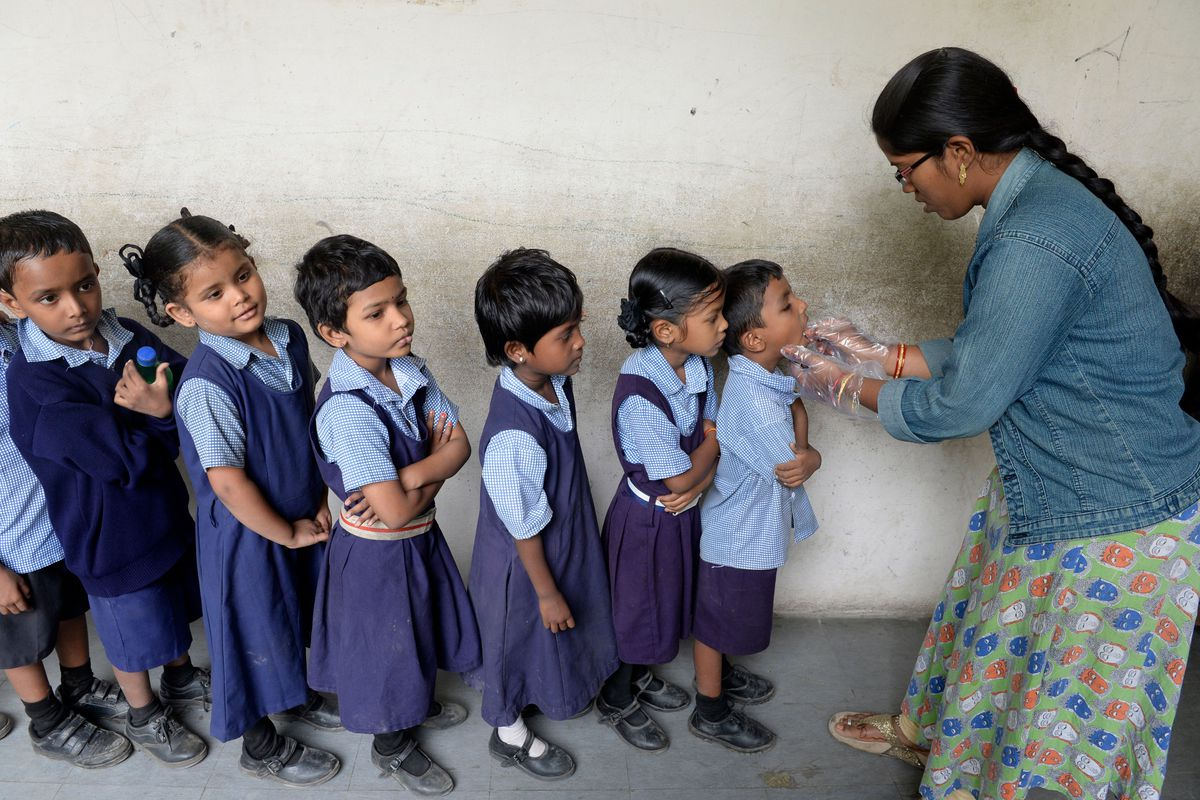 An adult administers oral medication to a line of elementary school children.