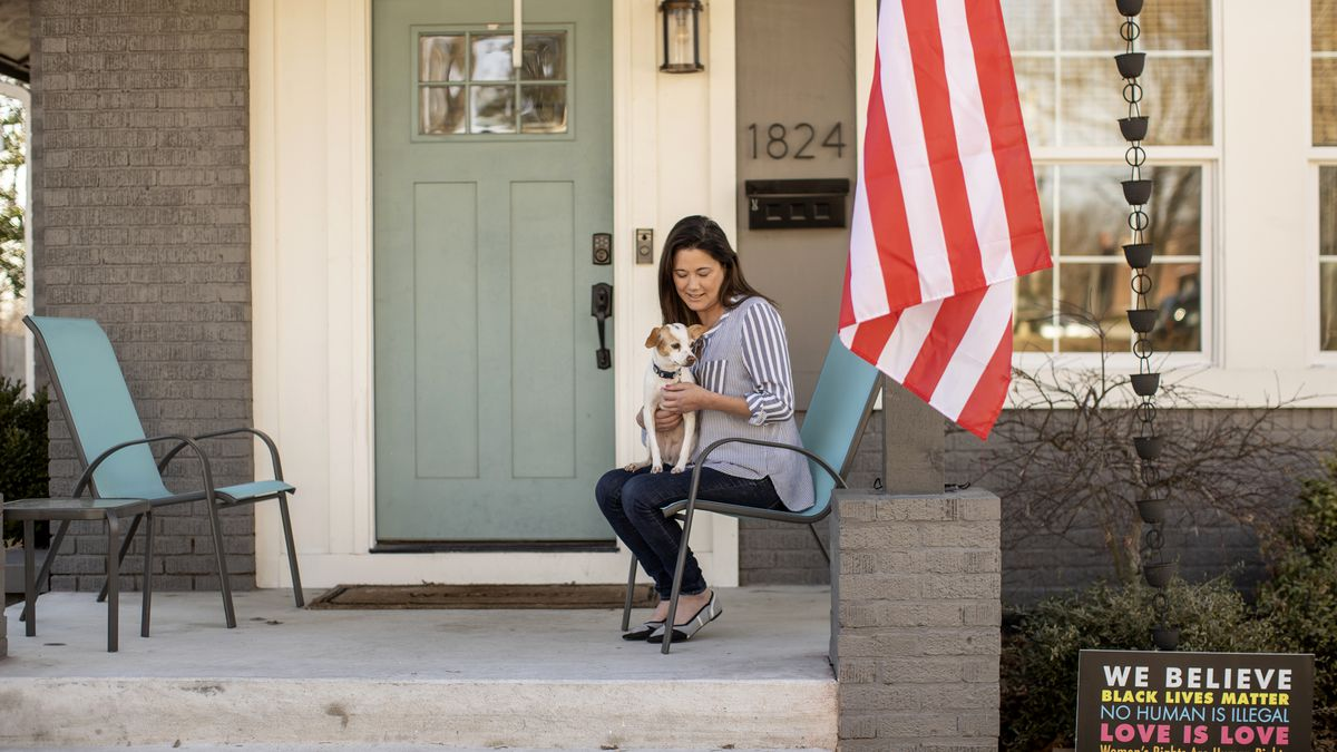Stephanie Robesky sits on the front porch at her home in the trendy Owen Park neighborhood just outside of downtown Tulsa, Okla., with her dog Tastee Mae on Jan. 9, 2021. Robesky moved to Tulsa as part of the George Kaiser Family Foundation's Tulsa Remote.