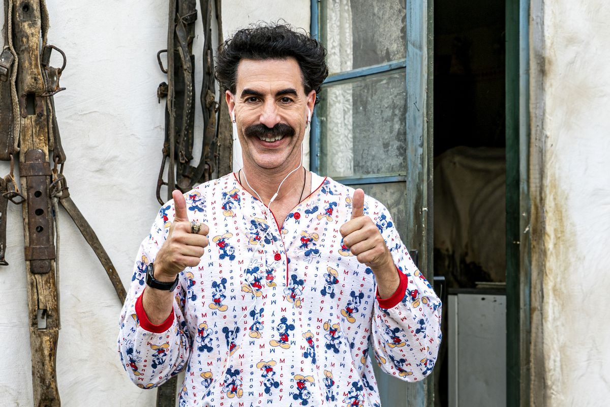 Borat grins with two thumbs up.