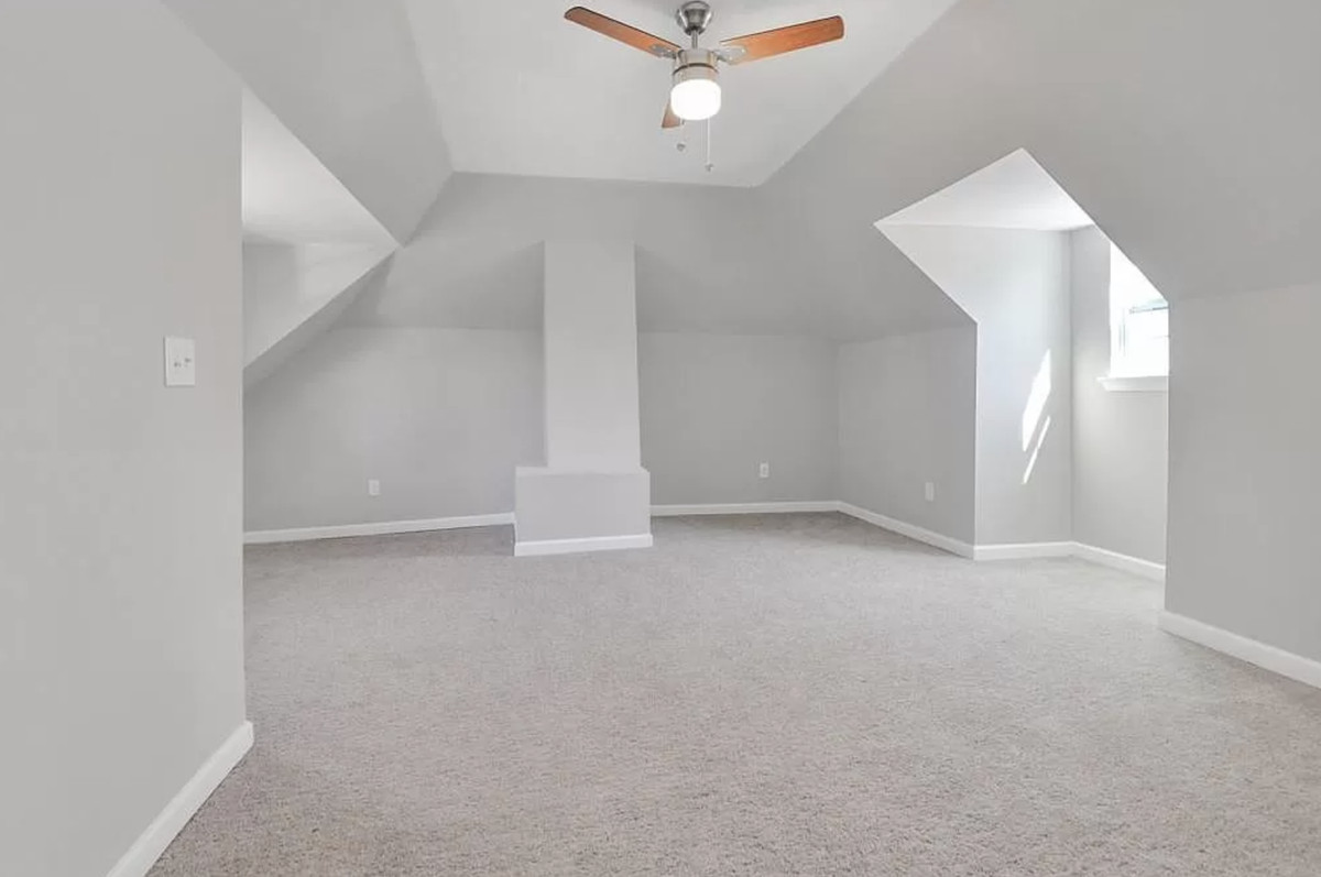 Large empty bedroom with light gray walls, gray carpet and ceiling fan.