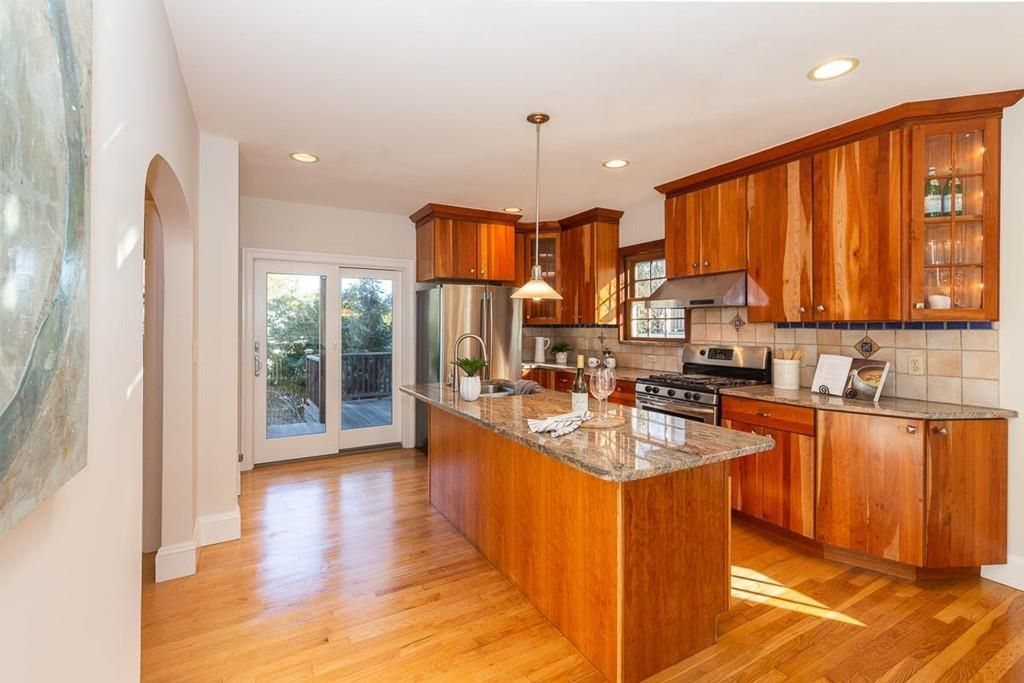 A large kitchen with an island in front of a counter with cabinetry above it.