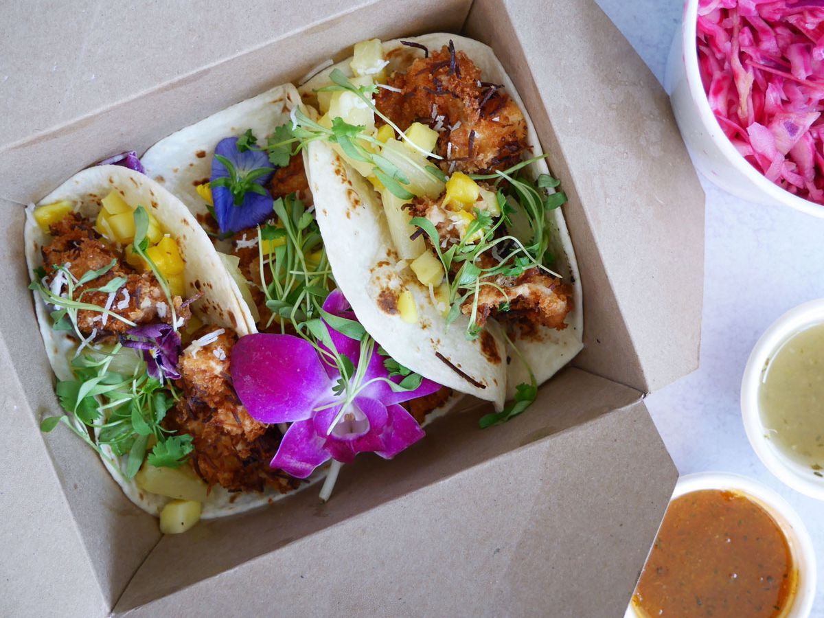 A photo of the vegan pea protein shrimp tacos from Sharks Cove, accompanied by cabbage slaw, pineapple hot sauce, and apricot pineapple sauce