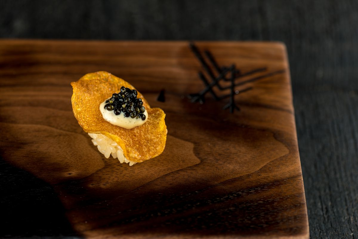 Potato chip nigiri with grilled ramp aioli and Ossetra caviar, placed next to the Robin logo