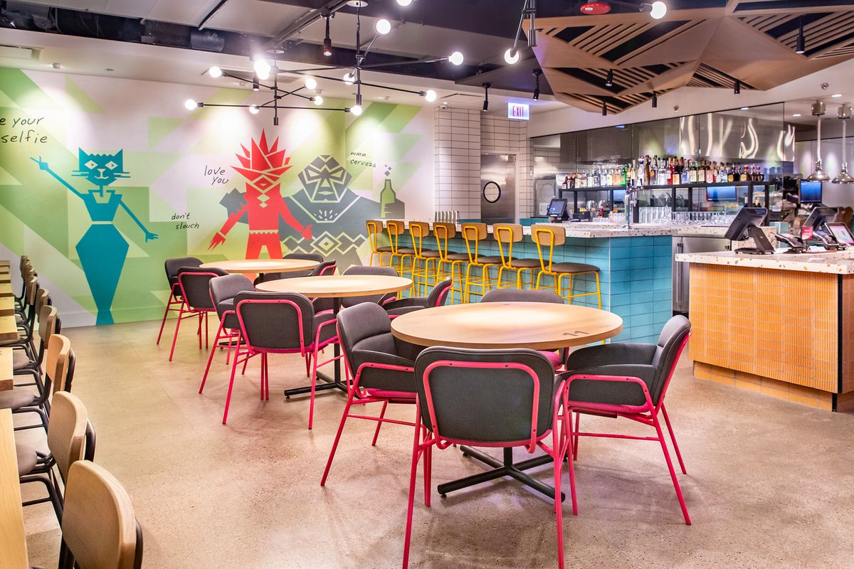 A casual restaurant space with round tables and a tiled high-top counter.