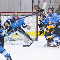 Buffalo Beauts Goaltender Amanda Leveille tracks a point shot through a crowd of skaters