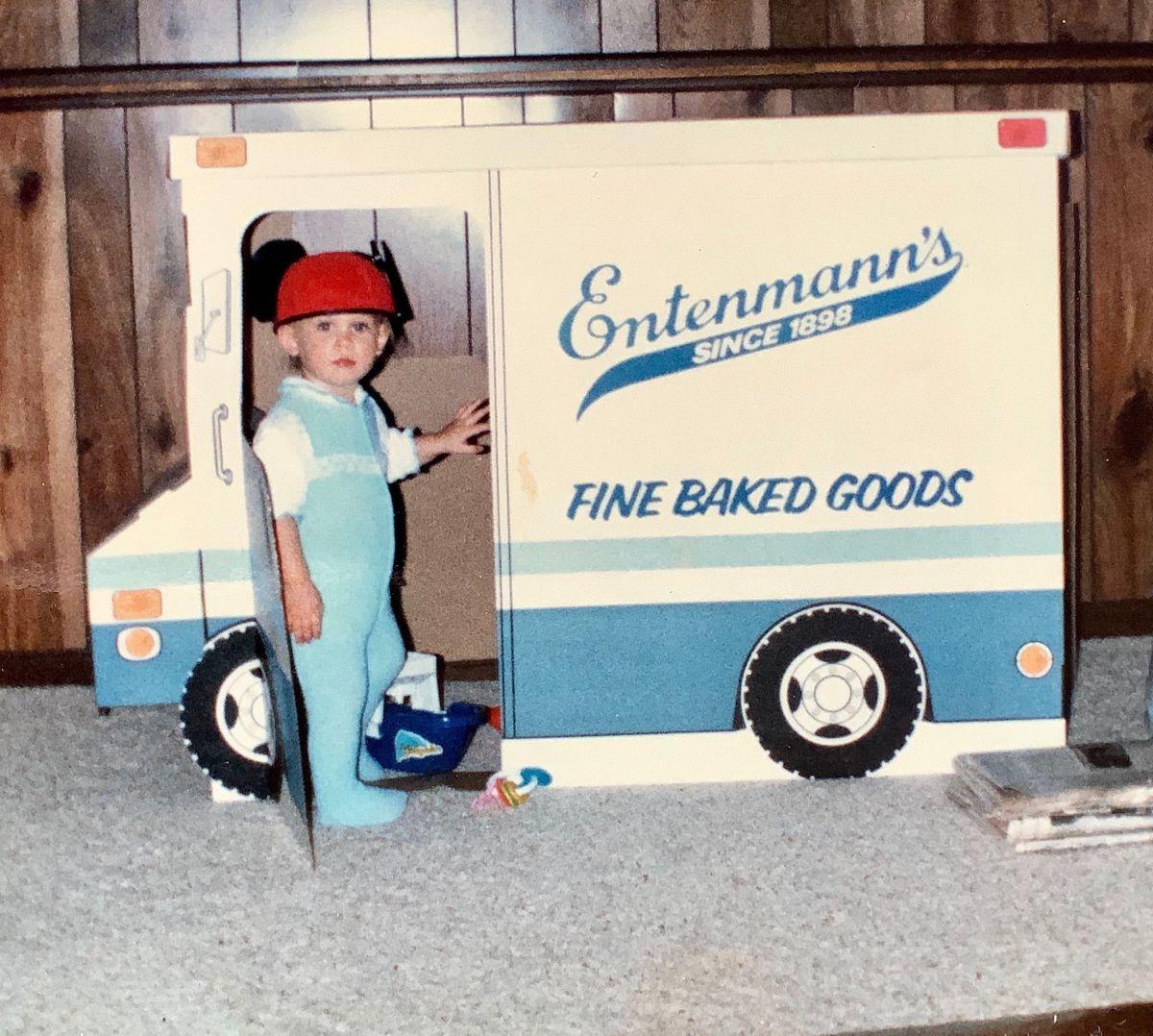 Photo des années 80 montrant un tout-petit portant une combinaison et un chapeau avec des oreilles de Mickey Mouse, debout à l'intérieur d'une découpe en carton d'un food truck d'Entenmann.