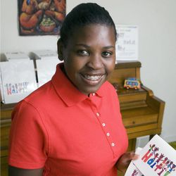 In an Aug. 28, 2012 photo, Sarah Cain, 14, holds postcards aty her home near Freeport, Ill., that she designed to sell to raise money to buy children's books for children in Haiti. Cain was adopted from Haiti when she was an infant.