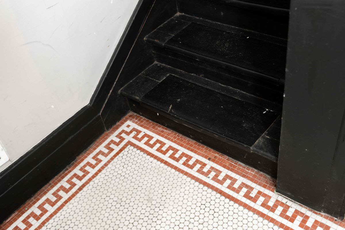 Close up of a black staircase with red and white tile pattern at the base.