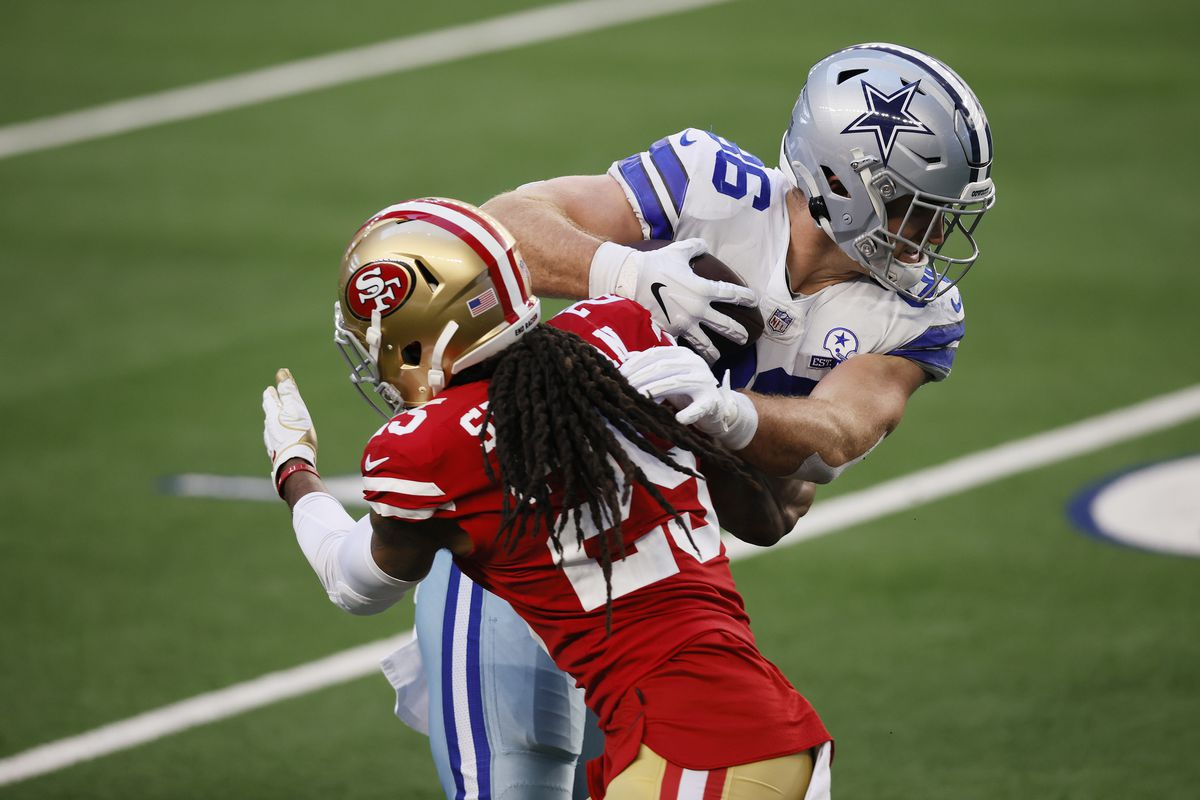 Tight end Dalton Schultz #86 of the Dallas Cowboys runs for a touchdown against cornerback Richard Sherman #25 of the San Francisco 49ers during the third quarter at AT&T Stadium on December 20, 2020 in Arlington, Texas.